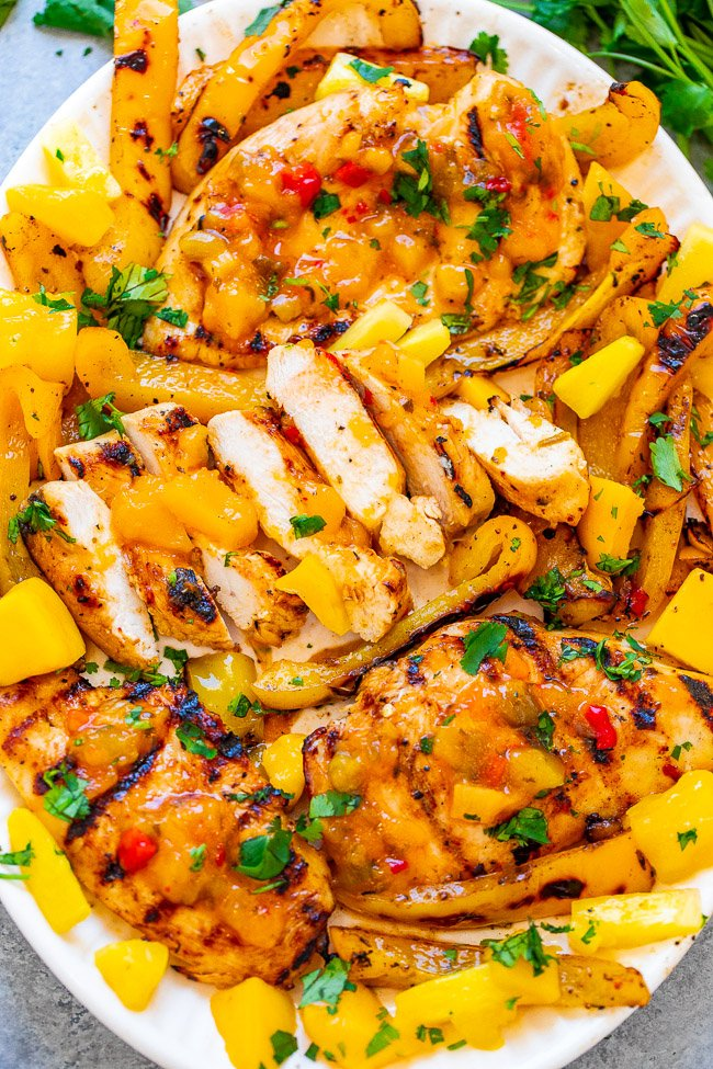 Grilled Mango Pineapple Chicken - EASY, ready in 10 minutes, and the flavor of the juicy chicken makes you feel like you're on a TROPICAL island!! Grilled peppers on the side makes for the PERFECT summer meal that's HEALTHY and DELICIOUS!!