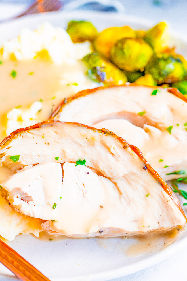 Two slices of herb roasted turkey on a white plate with mashed potatoes, gravy, and Brussels sprouts.