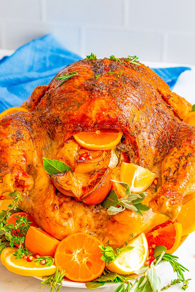 View of an oven roasted turkey stuffed with citrus fruits and herbs.