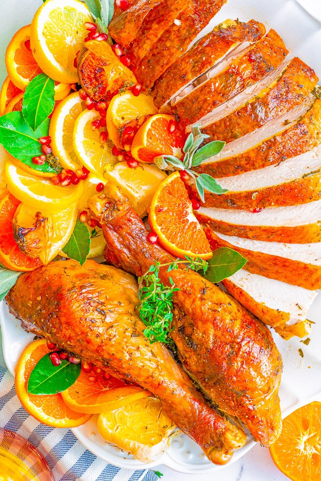 Overhead view of a sliced oven roasted Thanksgiving turkey with citrus fruit and fresh herbs.