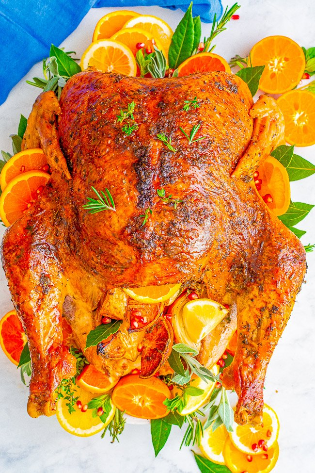 Overhead view of a roasted Thanksgiving turkey surround by citrus slices and fresh herbs.
