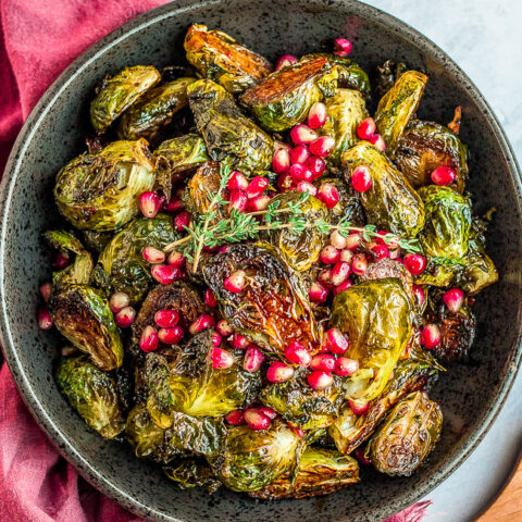 Balsamic Glazed Brussels Sprouts with Pomegranate Seeds - An easy side dish that's perfect for not only the holidays but anytime you're in the mood for CRISPY roasted Brussels sprouts!! The homemade balsamic glaze seeps into every inch of the spouts and adds so much tangy-sweet flavor!!