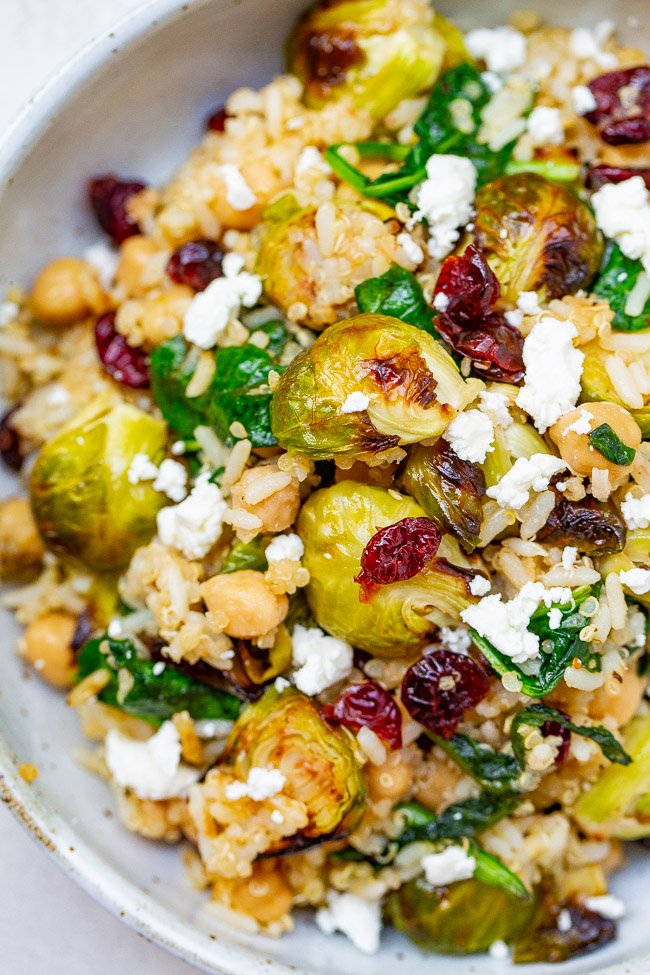 Roasted Brussels Sprouts Quinoa Chickpea Salad - A HEARTY salad that celebrates the flavors of fall including roasted Brussels sprouts and dried cranberries along with quinoa, chickpeas, spinach, and goat cheese!! Perfect for lunch, a meatless main, or a HEALTHY side dish on your holiday table!!