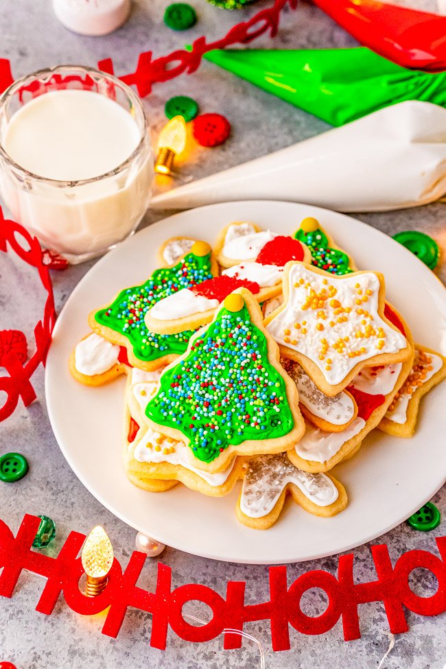 Christmas Cut Out Cookies — These traditional cut out sugar cookies are just like Grandma used to make!! They're thin but still soft, topped with a simple 2-ingredient royal icing, and loaded with sprinkles! So festive and perfect for cookies exchanges or hostess gifts!!