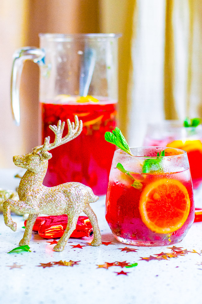 Pomegranate Mojito Punch - A FESTIVE twist on a classic mojito complete with pomegranate juice and pom arils while retaining plenty of fresh mint and of course the rum!! Fast, easy, SO TASTY, and perfect for holiday entertaining!!