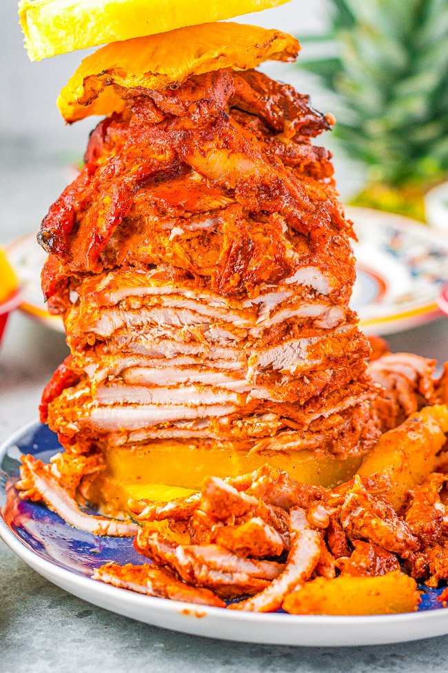 Tacos Al Pastor - Learn to make this staple Mexican recipe that includes thinly sliced pieces of pork marinated in a tangy, sweet pineapple sauce AT HOME! Juicy, flavorful, tender pork served in tortillas with onions, cilantro, lime juice, and salsa! You'll want every night to be taco night!