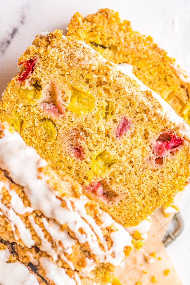 Strawberry Rhubarb Bread - This EASY, no-mixer quick bread is full of spring and summer flavors! Sweet strawberries and tart rhubarb are used to make this delightful bread that's topped with a buttery CRUMBLE and then GLAZED! that is perfect for breakfast or dessert!