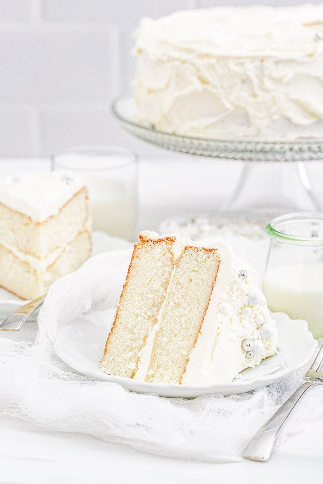 White Layer Cake – A classic, white, two-layer cake recipe for cake with a light texture that's complemented by super light and fluffy buttercream that's not too sweet! Learn how to make THE BEST white layer cake that's fancy enough to serve at your most special celebrations and events!