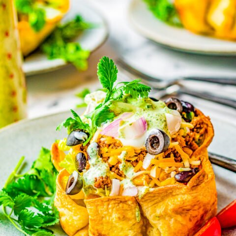 Beef Taco Salad Bowls - Making homemade taco salad bowls is so easy and they're perfect for holding this family-favorite taco salad including seasoned ground beef, black beans, cheese and more! Everything is topped with a creamy lime-cilantro dressing that'll have everyone finishing their salad!