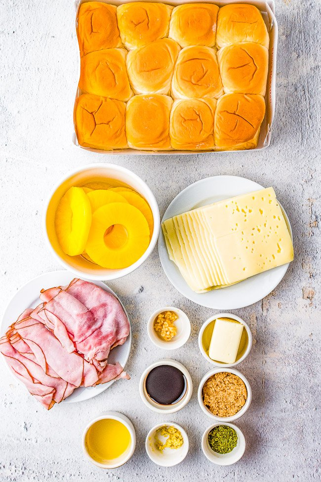 Hawaiian Ham and Cheese Sliders - Grilled pineapple slices brushed with a soy and ginger marinade add a Hawaiian-inspired twist to these irresistible sandwiches! Juicy ham, melted Swiss cheese, and melted butter are impossible to resist! FAST, EASY, perfect as a game day or party appetizer, snack, or quick weeknight dinner!