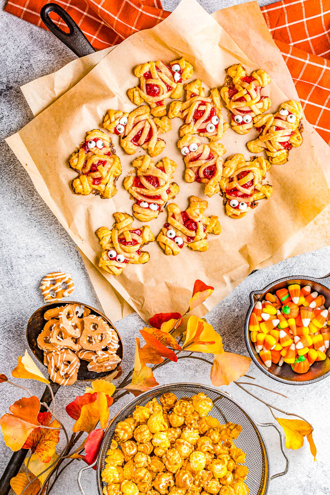 Mummy Hand Pies - A FUN and EASY Halloween treat that kids and adults alike both love! Buttery flakey pie crust with tangy-sweet cherry pie filling give great flavor to these festive and whimsical little goodies! Use store bought pie crust to save time and they're ready in 45 minutes. These little mummies will be the hit of your Halloween party!